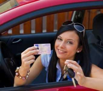 Девушка сидит в машине и показывает права