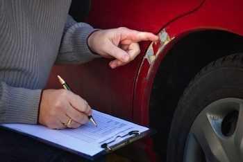 Оценщик оценивает ущерб автомобиля