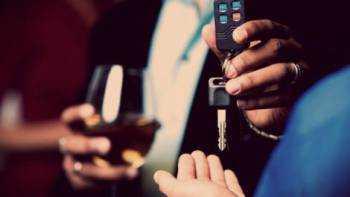 мужчина с бокалом в руке отдает ключи от машины